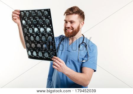 Portrait of a positive smiling medical doctor looking at CT scan isolated on white background