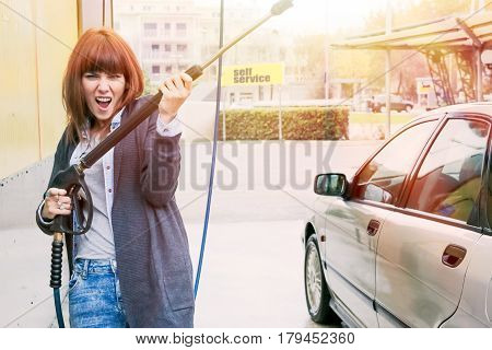 woman washing her car at car-wash self service station and making a funny gesture and cheerful expression