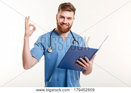 Portrait of happy confident doctor or nurse with clipboard in hand showing okay gesture isolated on white background