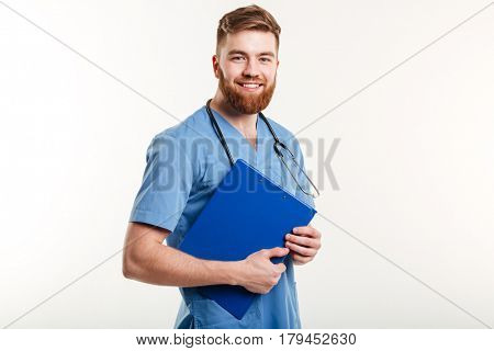 Portrait of a young friendly doctor or nurse with stethoscope holding clipboard and looking at camera isolated on the white background