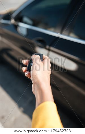 Closeup of woman hand holding keys and closing the door of her car