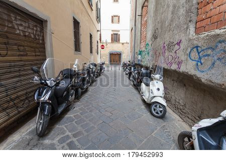 Florence ITALY- September 11 2016: A lot of scooters and mopeds of local citizens are parked in the narrow street in Florence