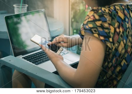 Asian woman using smartphone at home while working with laptop computer. Online business and wireless working from anywhere concept with vintage filter effect