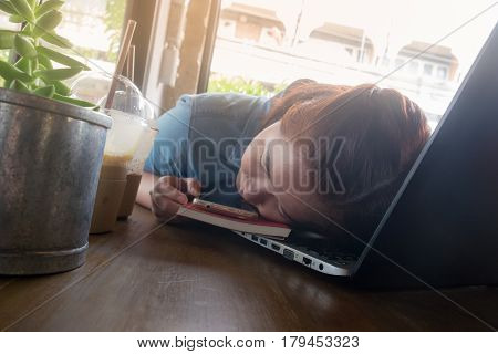 Young Hipster woman sleeping while working working with laptop computer in coffee shop. exhausted worker on busy day. Freelance business activity concept.