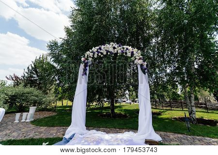 Wedding arch with flowers and white cloth near the birch