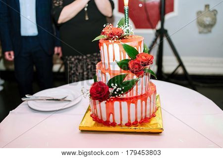 White wedding three-tiered cake with red glaze and roses