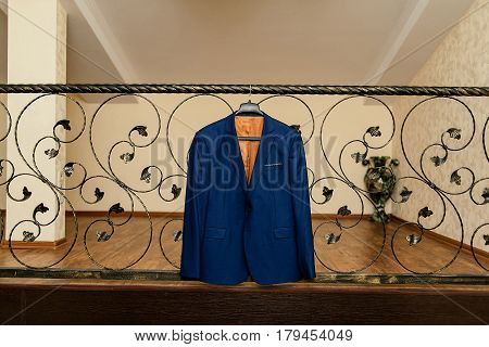 Beautiful blue groom's jacket hanging on the wrought-iron railing