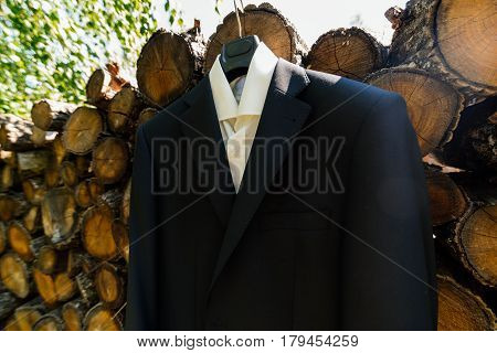 The shirt and jacket of the groom hang on a clothes hanger next to a stack of wood