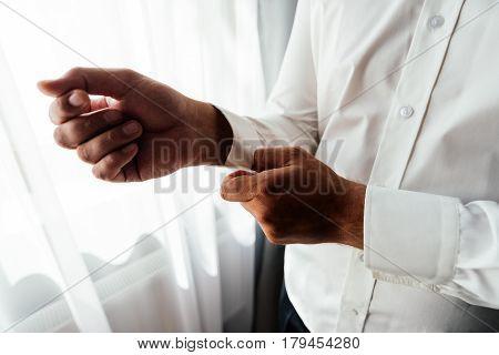 A man in a white shirt buttoning a button on a shirt cuff