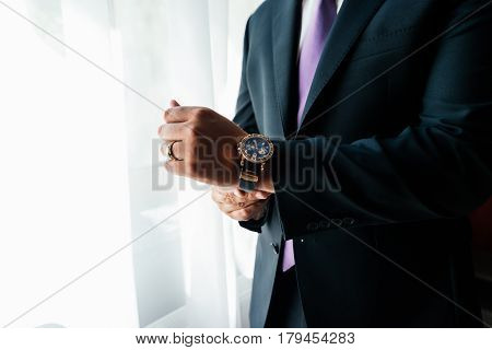 Watch on the wrist of a man in black suit.