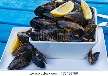 Cooked Mussels In A Dish With Lemon Wedges