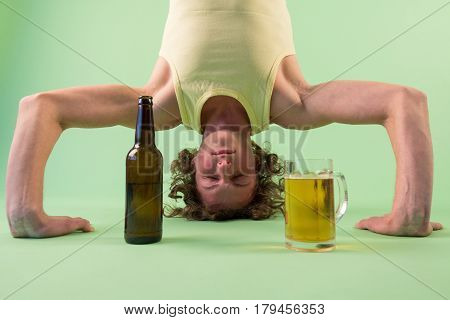 Caucasian man doing yoga with beer headstand pose