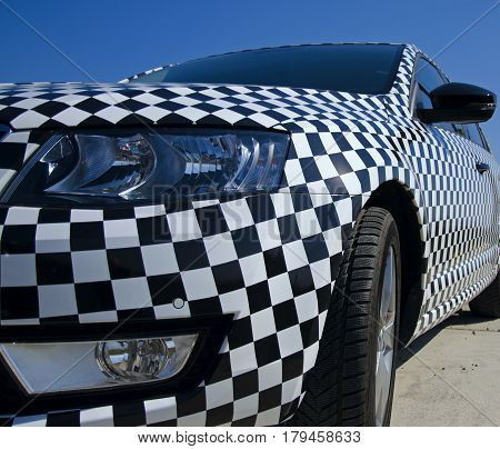 Closeup view of the car checkerboard pattern with detail headlight and rearview mirror with blue sky