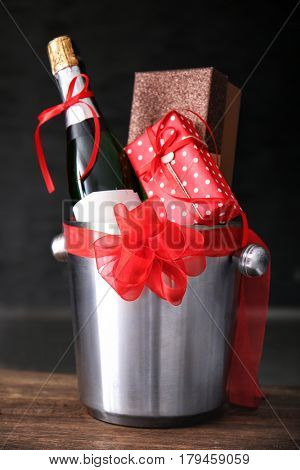 Wine bottle and gift boxes in bucket on dark background