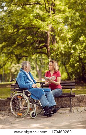 Young carer woman reading book in the park  disabled senior man in wheelchair