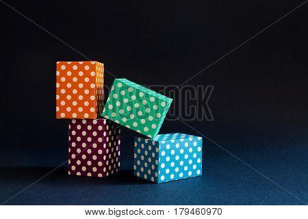 Multicolor polka dot blocks pattern composition. Violet green orange blue color rectangular boxes construction on dark blue black paper background. Geometrical design and minimalism concept photo.
