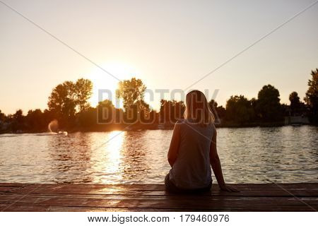 Woman from back sitting alone on dock and looking sunset