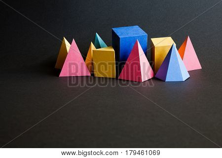 Colorful abstract geometric solid figures on black background. Pyramid prism rectangular cube yellow blue pink green colored figures. Black textured paper, shallow depth of field, copy space.