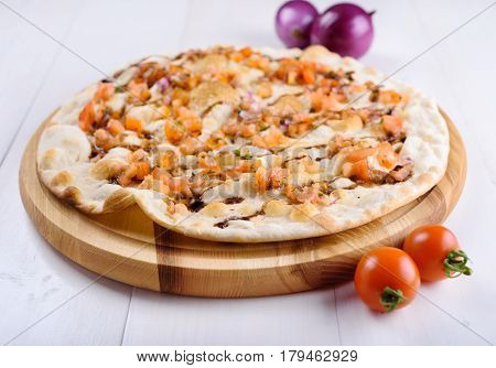 Focaccia with tomato and onions on a wooden board on a white background
