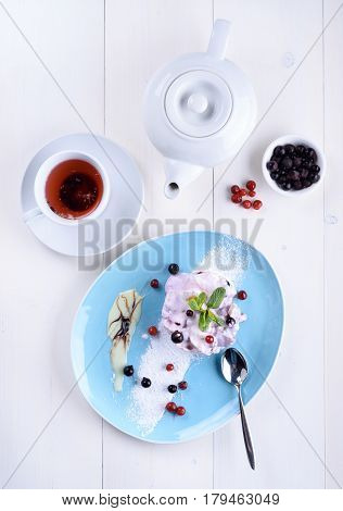 Cake with fresh berries on a blue plate next to a cup of tea and a teapot. Berry cake with tea