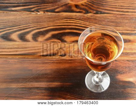 Cognac is poured in a shot glass. The shot glass is on a wooden table