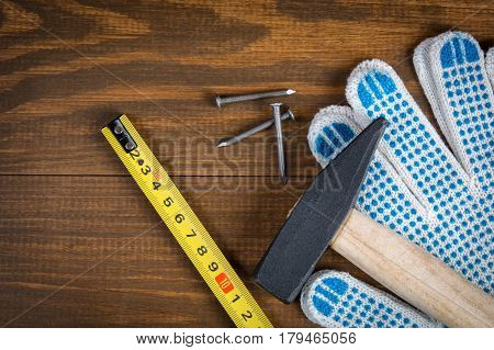 Hammer nails roulette (tape measure) and construction gloves on a wooden background roulette and construction gloves