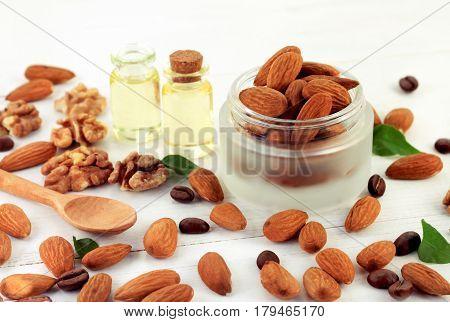 Raw Nuts in cosmetic jar, almond and walnut, oil bottles in background. Application for skin treatment. Healthy beauty care.