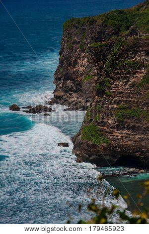 Scenic Seascape: A Powerful Cliff On The Indian Ocean. Turquoise Sea Water With White Foam Meet Roug
