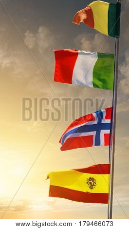 Mast with flags of different countries at sunset