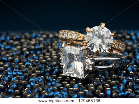 Pair of jewelry rings with big diamonds on blue background