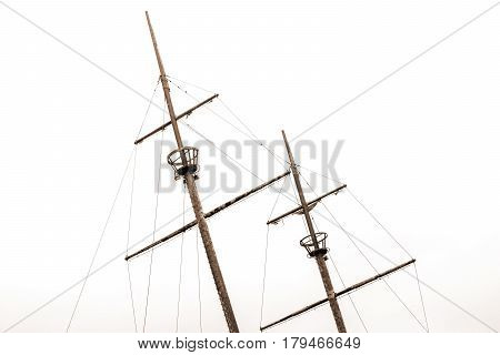 Old shipwreck masts with crows nests and old sails leaning to left with sky background sepia tone