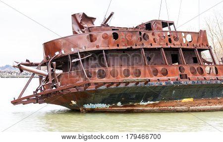 Bent and broken shipwreck marooned near shore closeup detail