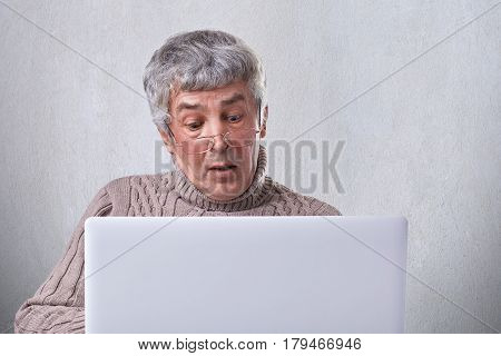 A portrait of surprised mature man in glasses having puzzled expresion while looking into the screen of a laptop. A senior man shocked while reading messages on computer isolated over white wall.