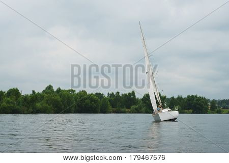Sailing, yachting. Walk on a sailing yacht on the pond, the lake, on a cloudy summer day. Large white sailing boat during the boat ride, or regatta. Summer vacation on the beach.