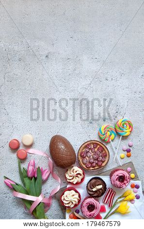 Assorted easter sweets bakery cupcakes chocolate eggs and confectionery with background space