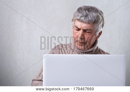 A mature man with gray hair siting in front of his laptop having dissatisfied expression and wrinkles on his face isolated over white background. People emotions technology and lifestyle concept.