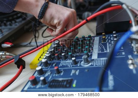 Musician adjusts audio equipment. Man sets the audio level on the console audio effects. Male hand tunes DJ equipment.