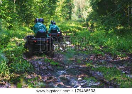 Summer Activities for adults - a trip on quad bikes on the road. Man on ATV in the mud on the road to take part in the race over rough terrain in the forest on a hot summer day.