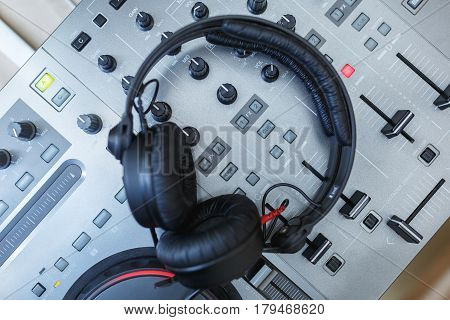 Top view of DJ Mixer with headphones. Elements and details of artists working tools - DJ console with knobs and black headphones. Soft focus.