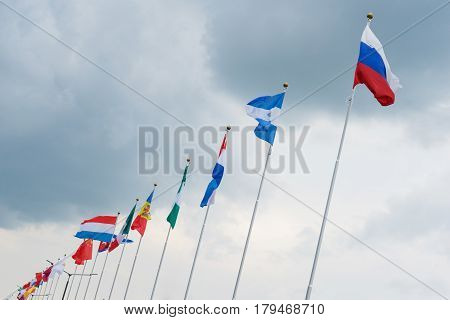 national flags of several world countries fluttering in the wind with the backgrounds of the cloudy sky. flags of the world countries on the flagpole.