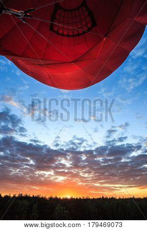 a red air balloon heart form rises up at dawn