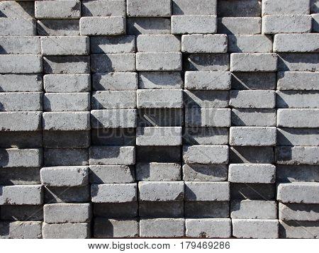 Uneven Stack of Grey Concrete Road Bricks Background