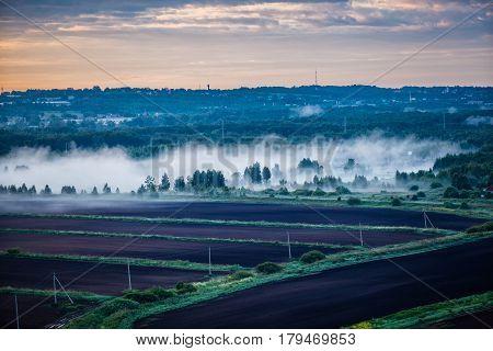 Aerial photo of agricultural russian village, dawn fog