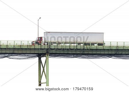 A semi-truck crosses a high bridge in front of a blank white sky with lots of copy space