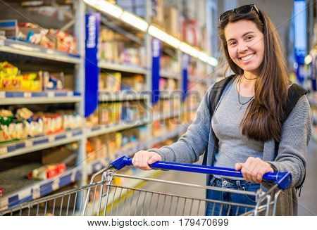 happy young woman pushing trolley in supermarket choose products