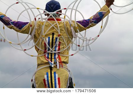 Colorful Native American Hoop Dancer Against a Gray Cloudy Sky