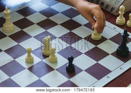 Sports and hobbies - a game in rapid chess. Child hand makes a move on the chessboard. Chess pieces on the board during the game in fast chess.