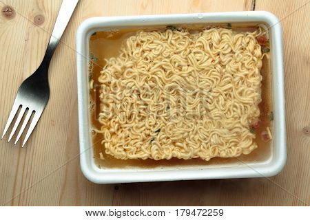Nourishing noodles on a wooden table in a disposable plate. Top view.