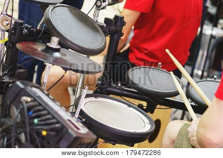 The musician plays on an electronic drum set. Moment musical performances on stage. Playing an electronic drum.