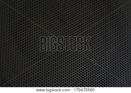 Abstract background is a black metal grid for the speaker close-up. Details audio equipment. Soft focus.